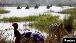 Des Nigérians fuyant les attaques de Boko Haram entrent au Tchad; des hommes traversent le lac Tchad à dos de chameaux, près d'un où une femme nettoie des habits , à Ngouboua, le 19 janvier 2015.