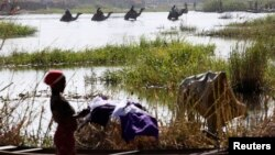 FILE - Men on camels cross the water as a woman washes clothes in Lake Chad at Ngouboua.