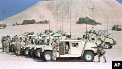 FILE - U.S. Marines tend to a row of parked humvees with TOW anti-tank missile launchers mounted on them at a desert camp in Saudi Arabia during the Gulf War, Jan. 26, 1991.