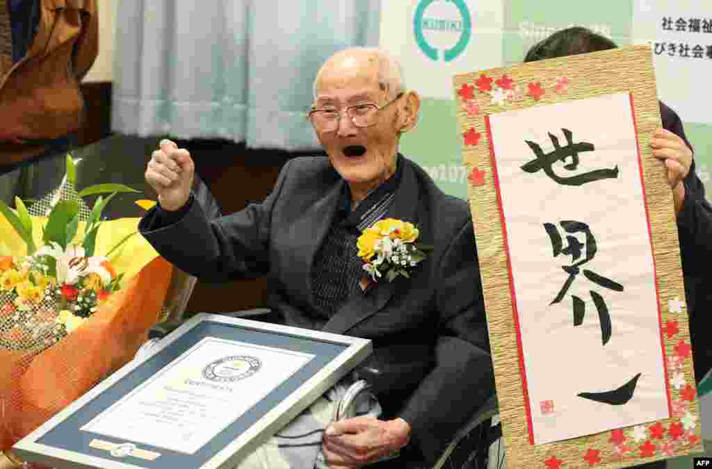 In this Japan picture received through Jiji Press, 112-year-old Chitetsu Watanabe stands next to a sign reading, in Japanese, 'World Number One' after he was officially recognized as the world's oldest living male, in Joetsu, Niigata prefecture.
