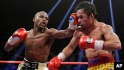Floyd Mayweather Jr., left, hits Manny Pacquiao, from the Philippines, during their welterweight title fight in Las Vegas, Nevada, May 2, 2015. (AP Photo/Isaac Brekken)