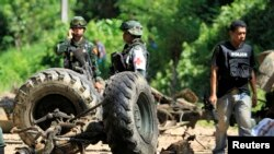 Thai security personnel inspect the wreckage of a military truck after a bomb attack by suspected Muslim militants on a roadside in Yala province, south of Bangkok June 29, 2013. Suspected Muslim rebels in southern Thailand killed eight soldiers in the ro