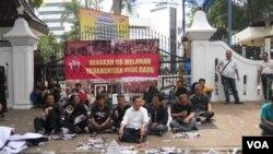 Panitia pertemuan aktivis 98 saat melakukan aksi protes di depan gerbang Kemenpora Jakarta dengan menggelar foto-foto 13 korban penculikan aktivis 97-98, Selasa, 24 Juni 2014. (Foto: dok)