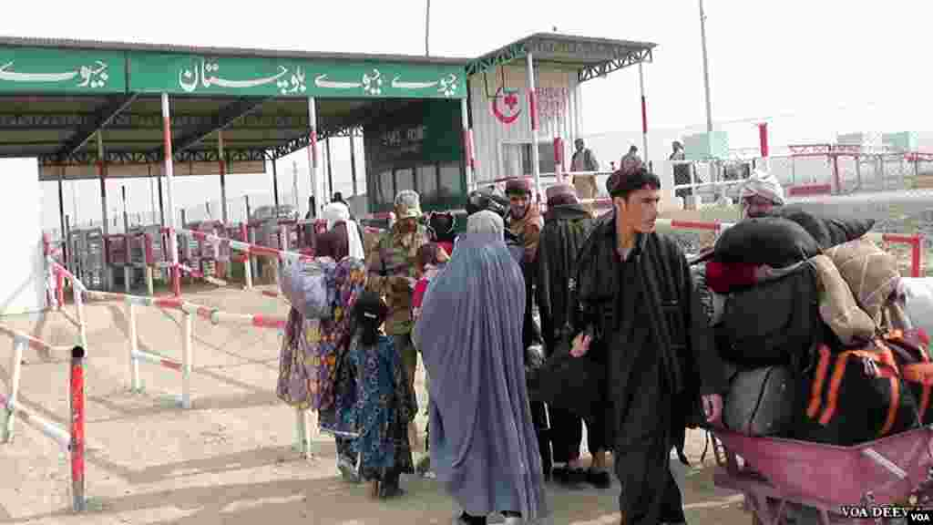 سیکورٹی اہکار سفر کرنے والوں کے دستاویزات کی جانچ کرتے ہوئے