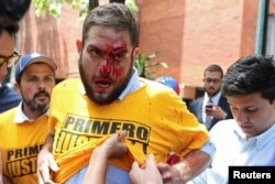 FILE - Juan Requesens, deputy of the Venezuelan coalition of opposition parties (MUD), is helped after being injured in clashes with pro-government supporters outside the offices of the Venezuela's ombudsman in Caracas, Venezuela, April 3, 2017.