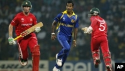 Sri Lankan bowler Nuwan Kulasekara, center, runs along with Zimbabwe's batsmen Brendan Taylor, left, and Regis Chakabva during the Cricket World Cup match between Sri Lanka and Zimbabwe in Pallekele, Sri Lanka, Thursday, March 10, 2011. (AP Photo/Eranga J