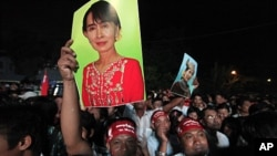 4月1日在仰光缅甸全国民主联盟总部的门前,支持者高举昂山素季的肖像,庆祝昂山素季胜选