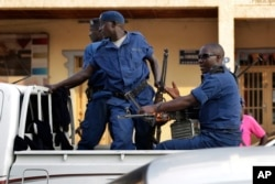 FILE - Police drive by the scene of a grenade attack on a parked car downtown Bujumbura, July 20, 2015.