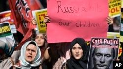 Manifestantes en Estambul portan carteles y una foto representando al presidente ruso, Vladimir Putin, durante una protesta contra las operaciones militares rusas en Siria, el sábado, 3 de octubre de 2015.