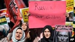 Phụ nữ xuống đường ở Istanbul cầm biểu ngữ với hàng chữ 'Nga giết trẻ em của chúng tôi' và hình ảnh miêu tả ông Putin trong một cuộc biểu tình phản đối hành động quân sự của Nga ở Syria, ngày 3/10/2015.