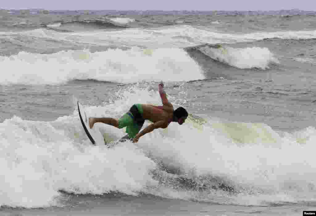 A surfer takes advantage of higher waves as winds from Hurricane Sandy began to affect weather in Boca Raton, Florida, October 25, 2012.