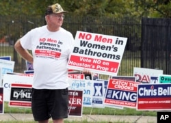 "FILE - A man holds a sign that reads, ""No men in women's bathrooms"" while protesting in Houston, Oct. 21, 2015."