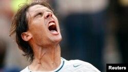 Petenis Spanyol unggulan keempat, Rafael Nadal merayakan kemenangan atas pemain Latvia, Ernests Gulbis di Roma (16/5).