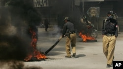 A Pakistani police officer tires set alight by protesters to condemn the killings of Shiite Muslims in Quetta, Pakistan, October 4, 2011.