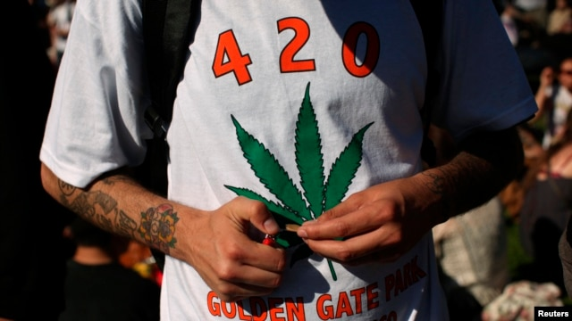 FILE - A man holds a joint during a gathering of marijuana advocates at Golden Gate Park in San Francisco, California.