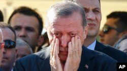 Turkish President Recep Tayyip Erdogan wipes tears during the funeral of Mustafa Cambaz, Erol and Abdullah Olcak, killed Friday while protesting the attempted coup against Turkey's government, in Istanbul, July 17, 2016.