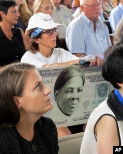 A woman holds a sign supporting Harriet Tubman for the $20 bill during a town hall meeting at the Women's Rights National Historical Park in Seneca Falls, N.Y.