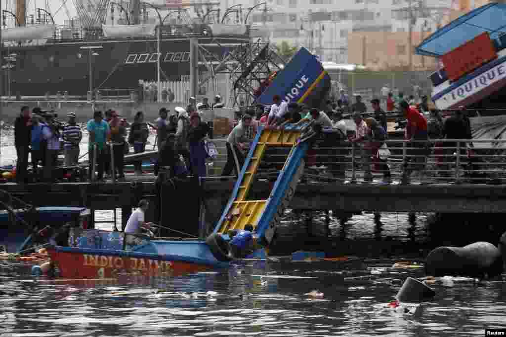 Para nelayan memeriksa kerusakan yang disebabkan gempa dan tsunami yang melanda pelabuhan Iquique di Chile utara (2/4).