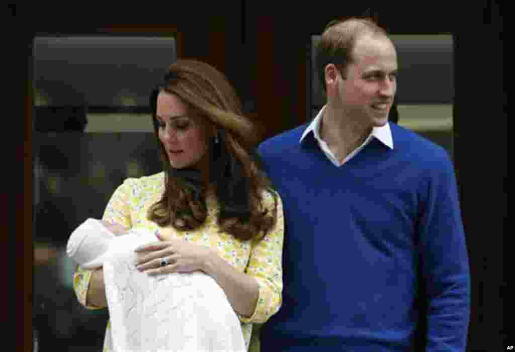 Britain's Prince William, right, and Kate, Duchess of Cambridge, pose for the media with their newborn daughter outside St. Mary's Hospital's exclusive Lindo Wing, London, Saturday, May 2, 2015. The Duchess gave birth to the Princess on Saturday morning.