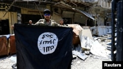 Arhiva - Pripadnik divizije za brza reagovanja drži zastavu militanata Islamske države u starom gradu Mosulu, Irak, 10. jula 2017.