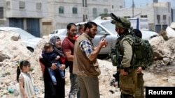 خانواده فلسطینی در ورودی شهر یاتا در کرانه باختری- ژوئن ۲۰۱۶