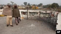 Dua warga India di pinggiran Jammu, India dekat perbatasan Pakistan, memeriksa rumahnya yang terkena tembakan dari Pakistan (3/1).
