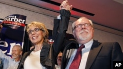 In an election to fill former Rep. Gabrielle Giffords, left, D-Ariz., congressional seat, Democratic candidate Ron Barber, right, celebrates a victory with Giffords and supporters at a post election event, in Tucson, Ariz, June 12, 2012 .