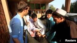 2018年6月16日在阿富汗賈拉拉巴德發生汽車炸彈事件後,一名受傷男子的親屬將他送入醫院。