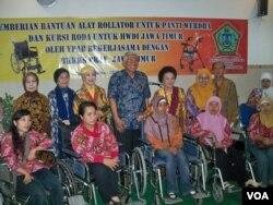Para disabilitas penerima bantuan kursi roda. (foto: VOA/Petrus Riski)