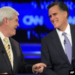 Former Massachusetts governor Mitt Romney, right, answers a question during the first New Hampshire Republican presidential debate on June 13, 2011.