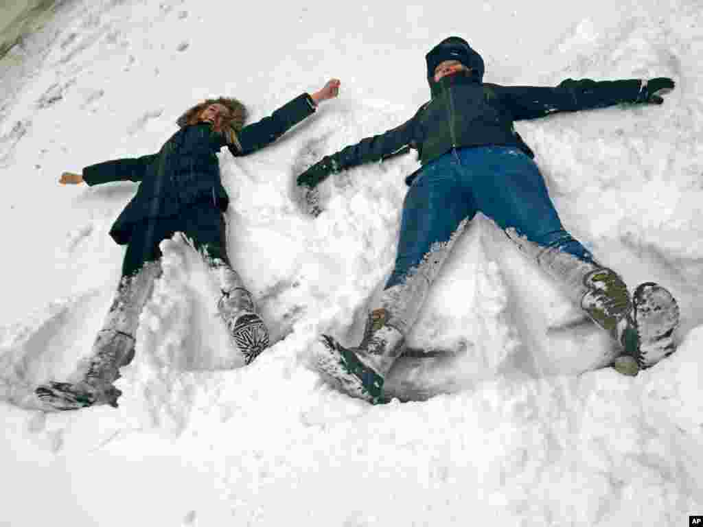 Bianca Hillier, left, of Columbus, Ohio, and Eloise Pollard of London take advantage of a snowtorm travel ban to do something they never envisioned: making snow angels on a normally busy stretch of Manhattan's Tenth Avenue at West 34th Street in New York, Jan. 27, 2015.