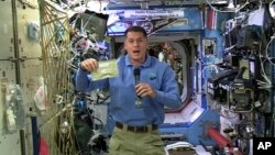 In this image taken from NASA video recorded Nov. 18, 2016, NASA astronaut Shane Kimbrough shows a pouch of turkey he will be preparing Thursday for the crew in celebration of the Thanksgiving holiday aboard the International Space Station.