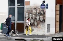 Pejalan kaki berjalan melewati karya seni seniman jalanan Perancis Christian Guemy, yang juga dikenal sebagai C215, untuk menghormati anggota majalah satire Charlie Hebdo,