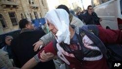 Người bị thương được đưa ra xe cứu thương sau vụ nổ tại trụ sở cảnh sát trong trung tâm thủ đô Cairo của Ai Cập, 24/1/14