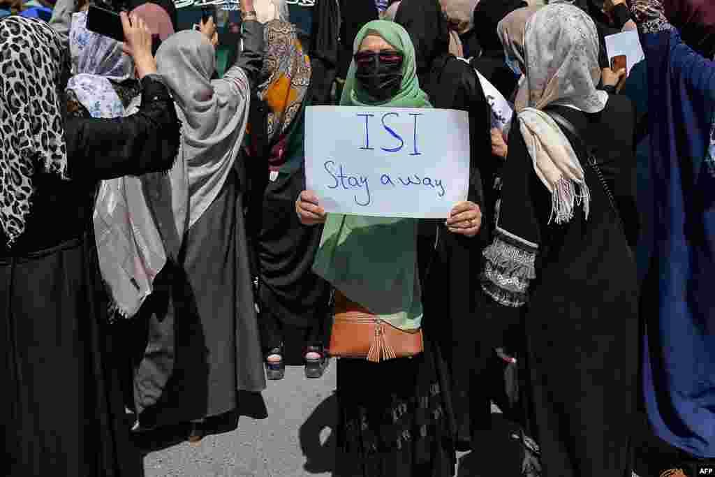 مظاہرے میں شریک ایک خاتون نے پلے کارڈ اٹھا رکھا ہے جس پر پاکستان کے خفیہ ادارے انٹر سروس انٹیلی جنس (آئی ایس آئی) تحریر ہے۔