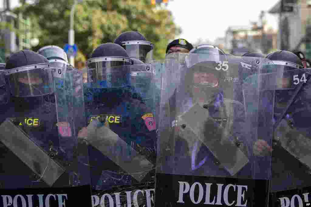 Police in riot gear stand guard as they face pro-democracy protesters during a rally in Bangkok, Thailand.