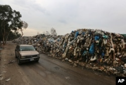 FILE - A car passes by a pile of garbage in Karantina, east Beirut, Lebanon, Dec. 17, 2015.