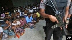 Seorang petugas polisi siaga saat kunjungan Duta Besar Bangladesh, Md. Nazmul Quaunine di tempat penampungan para migran di Langsa, Aceh (17/5).