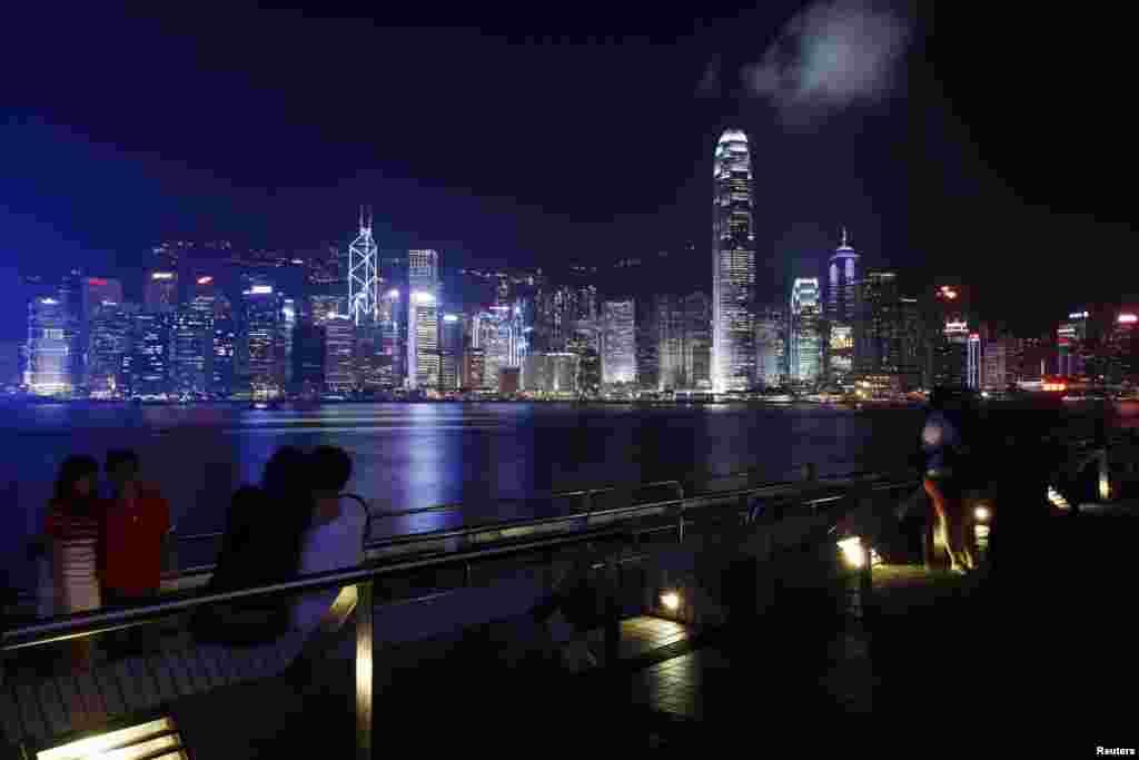 People rest along a waterfront at Hong Kong's Victoria Harbour facing the Hong Kong island side, China