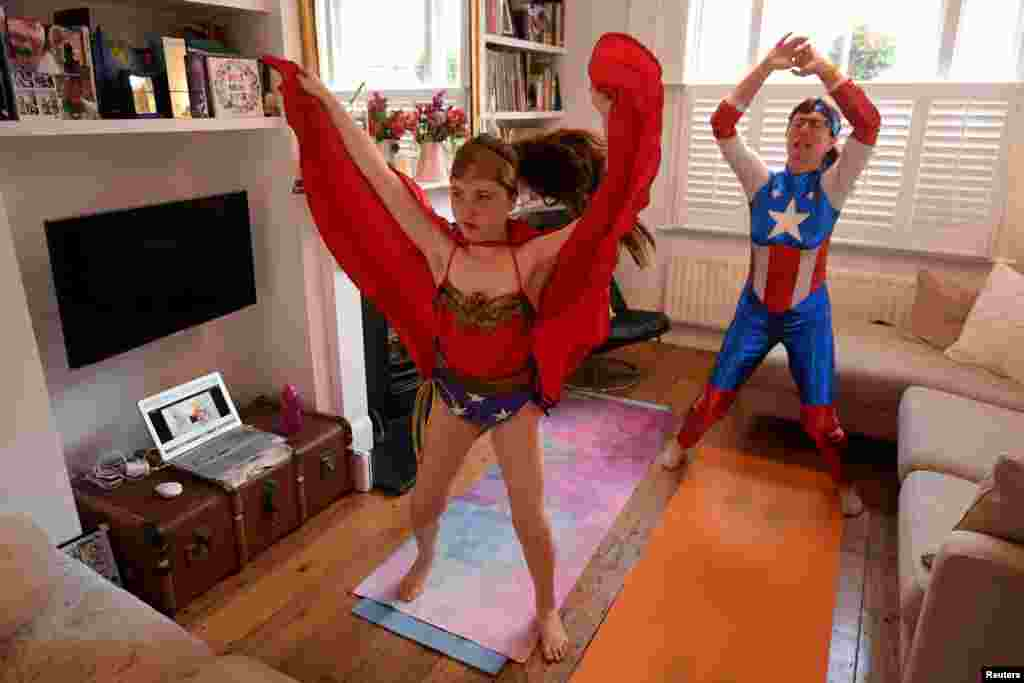 "Dressed as superheroes, Jo Proudlove and daughter Eve, 9, follow the daily online ""PE with Joe"" Joe Wickes' exercise class on ""Fancy dress Friday,"" at home in London, as the spread of the coronavirus disease (COVID-19) continues."