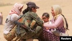 Kurd askari iroqlik qochqinlar bilan gaplashayapti.