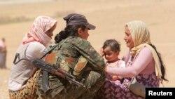 庫爾德軍人在接近敘利亞邊界附近協助逃避伊斯蘭國極端分子攻擊的雅茲迪人