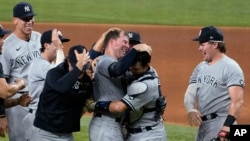 New York Yankees pitcher Corey Kluber, third from right, celebrates with catcher Kyle Higashioka, second from right, and the rest of the team after throwing a no-hitter against the Texas Rangers in a baseball game in Arlington, Texas, May 19, 2021. (AP Photo/Tony Gutierrez)