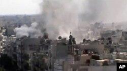 ຮູບຖ່າຍໂດຍມືກ້ອງສະໝັກຫຼິ້ນ ທີ່ນຳເຜີຍແຜ່ໂດຍຕາໜ່າງຂ່າວ Shaam ໃນວັນສຸກວານນີ້ ສະແດງໃຫ້ເຫັນ ເຫດລະ ເບີດທີ່ເມືອງ Khaldiyeh ທີ່ຕັ້ງຢູ່ໃກ້ໆເມືອງ Homs ໃນພາກກາງຊີເຣຍ (9 ມິຖຸນາ 2012)