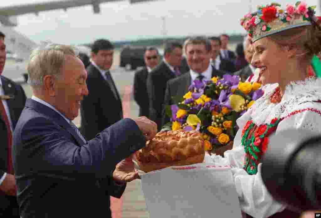Kazakhstan's President Nursultan Nazarbayev, left, gets traditional salt and bread upon arrival in Minsk, Belarus, Aug. 26, 2014.