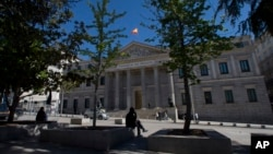 A man sits outside the Spanish Parliament in Madrid, Spain, May 3, 2016. Spain's King has signed a decree Tuesday dissolving parliament and calling elections for June 26 after deputies failed to agree on a new prime minister.