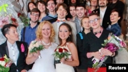 FILE - Two brides pose with their guests after their wedding ceremony at the wedding registry office in St. Petersburg, seemingly circumventing Russia's ban on same-sex marriages, Nov. 7, 2014.