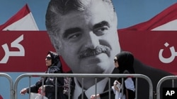 Lebanese women pass by a giant portrait of slain Lebanese Prime Minister Rafik Hariri near his grave in downtown Beirut, Lebanon, June 30, 2011.