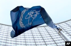 FILE - The flag of the International Atomic Energy Agency (IAEA) flies in front of the Vienna headquarters at the Vienna International Center, March 27, 2009.