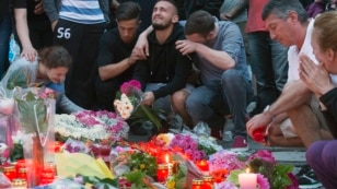 People mourn near the Olympia shopping center where a shooting took place the day before, leaving nine people dead in Munich, Germany, July 23, 2016.